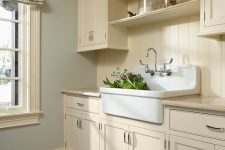 26 a buttercream laundry with shaker kitchen cabinets, printed textiles, a large sink and baskets for storage