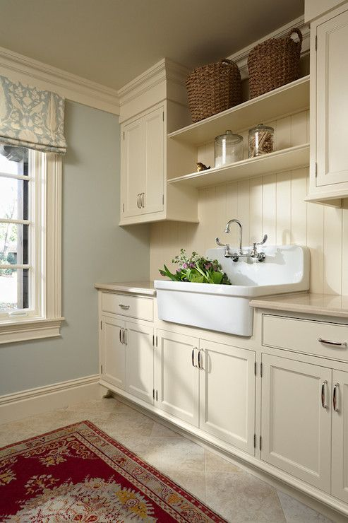 a buttercream laundry with shaker kitchen cabinets, printed textiles, a large sink and baskets for storage