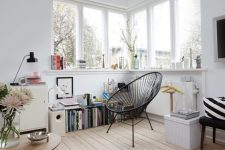 26 a lovely Nordic nook with a corner window, a windowsill used for storage, a black chair and a bookshelf is a very cozy corner
