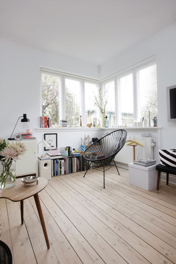 a lovely Nordic nook with a corner window, a windowsill used for storage, a black chair and a bookshelf is a very cozy corner