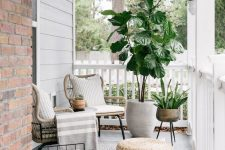 a modern porch with rattan chairs, a jute pouf, potted plants, a magazine stand and some neutral textiles is very chic