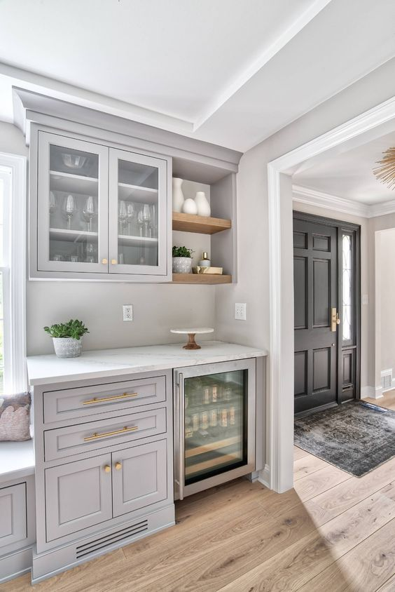 a light grey home bar done with kitchen cabinets, open shelves and a wine cooler is a lovely space for a farmhouse home