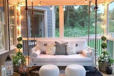 27 a welcoming modern porch with a suspended sofa, matching poufs, potted plants, candle lanterns and a bold geometric rug plus lights over the space