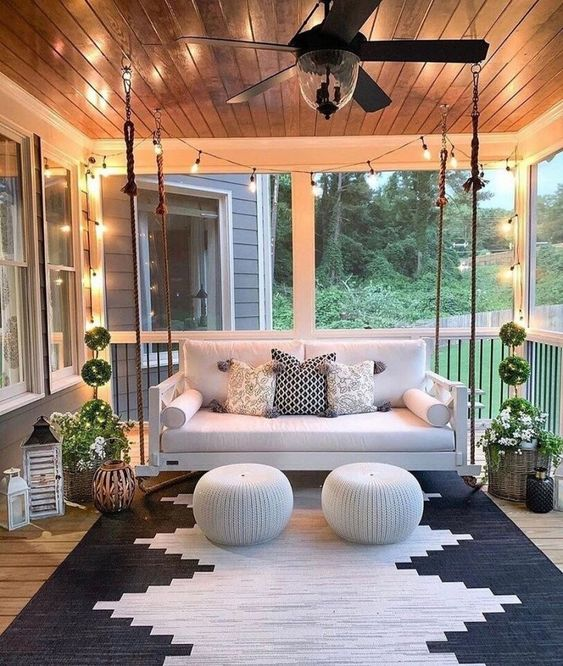 a welcoming modern porch with a suspended sofa, matching poufs, potted plants, candle lanterns and a bold geometric rug plus lights over the space