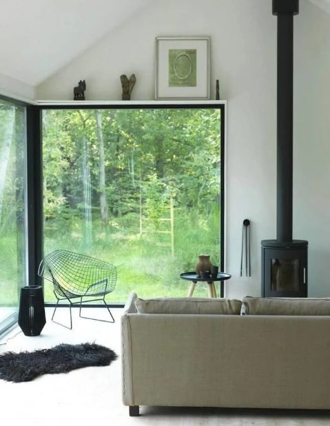 a contemporary living room with a corner window for gorgeous forest views, a hearth and cool furniture, some artworks over the window