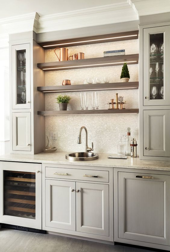 a large home bar done with neutral kitchen cabinets, with a large tile backsplash, open shelves, a wine cooler and additional lights