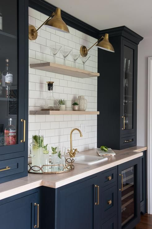 a large navy home bar done with shaker style kitchen cabinets, a blush countertop, open shelves and brass touches for more elegance