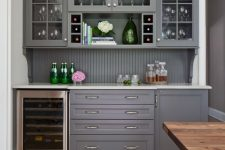 31 a chic grey home bar with kitchen cabinets – glass and usual ones, a beadboard backsplash and a wine cooler