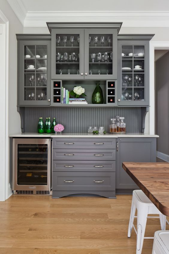 a chic grey home bar with kitchen cabinets - glass and usual ones, a beadboard backsplash and a wine cooler