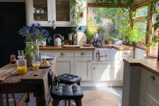 31 a cozy small cottage kitchen with a corner window, shaker cabinets, butcherblock countertops, a skylight over the space