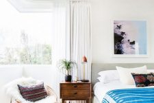 32 a gorgeous modern boho bedroom with a corner window, an upholstered bed, bright bedding and boho touches plus a chair by the window