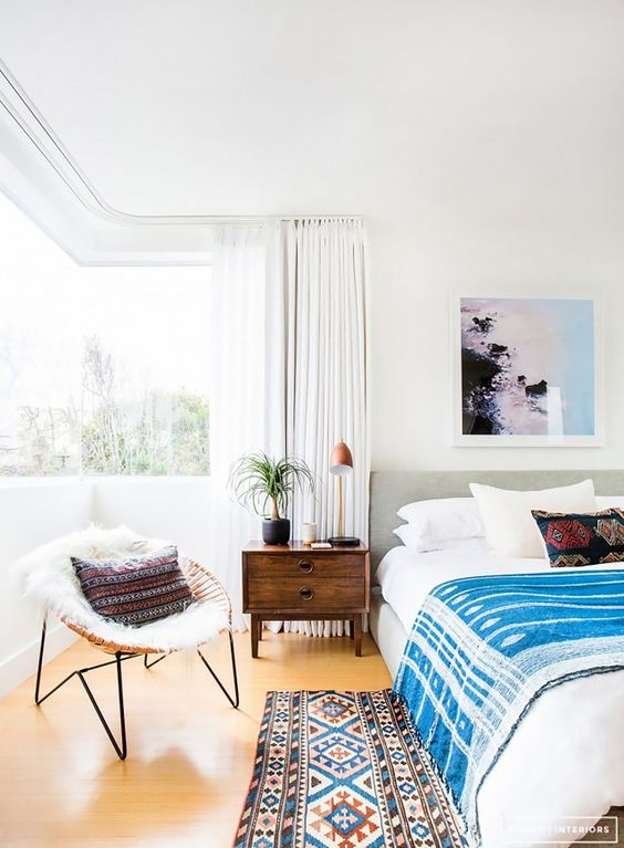 a gorgeous modern boho bedroom with a corner window, an upholstered bed, bright bedding and boho touches plus a chair by the window