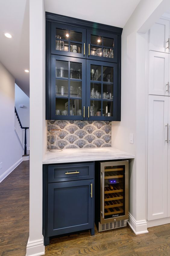 a tiny home bar done with a couple of navy kitchen cabinets and squeezed into a tiny awkward nook is lovely and has all the necessary stuff