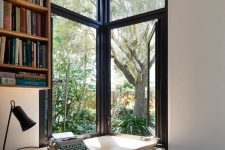 33 a home office nook with a corner window for natural light, fresh air and views, a floating desk, a small stool and a bookshelf on the wall