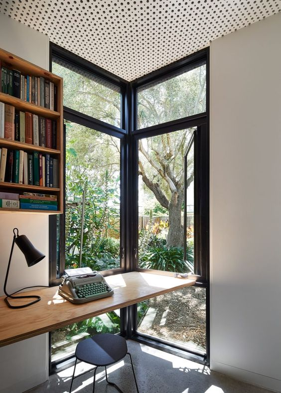 a home office nook with a corner window for natural light, fresh air and views, a floating desk, a small stool and a bookshelf on the wall