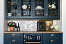 33 an elegant home bar done with navy kitchen cabinets, glass and usual ones, with a wine cooler and a subway tile backsplash plus a butcherblock countertop