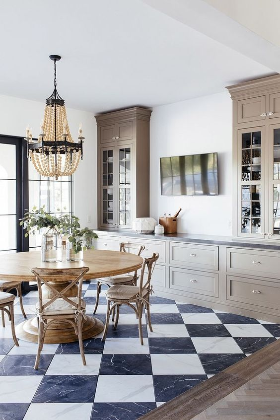 a beautiful farmhouse dining room done with grey kitchen cabinets, a wooden dining set and a wooden bead chandelier