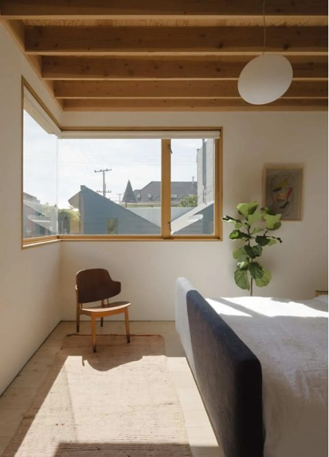 a simple and minimal bedroom with a corner window that brings natural light inside, with a chair and an upholstered bed