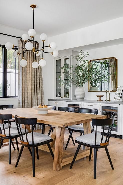 a stylish dining room with lower kitchen cabinets with glass doors, a wooden dining table and black chairs