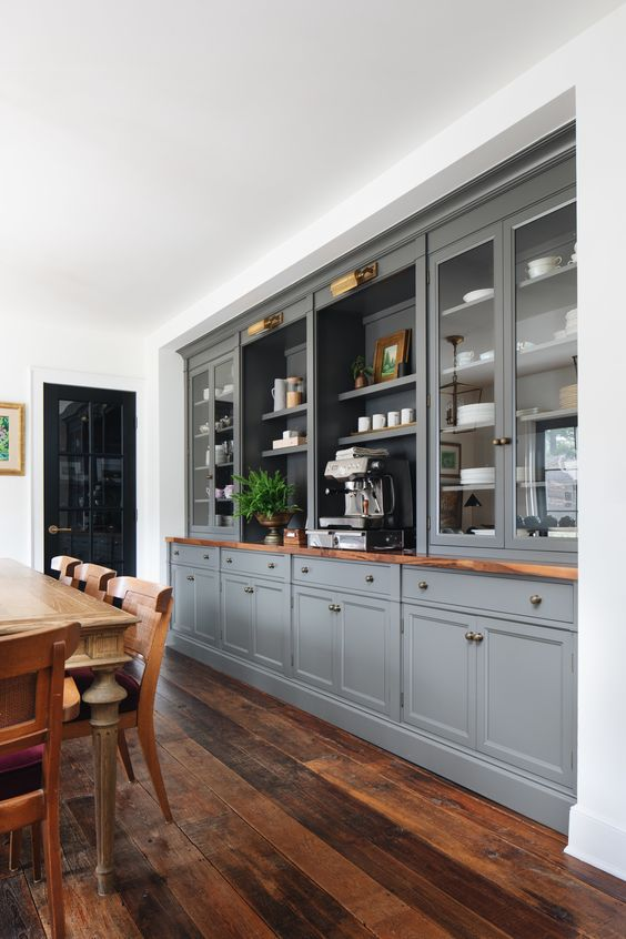 a formal farmhouse dining room with a whole wall taken by grey kitchen cabinets, a vintage wooden dining set