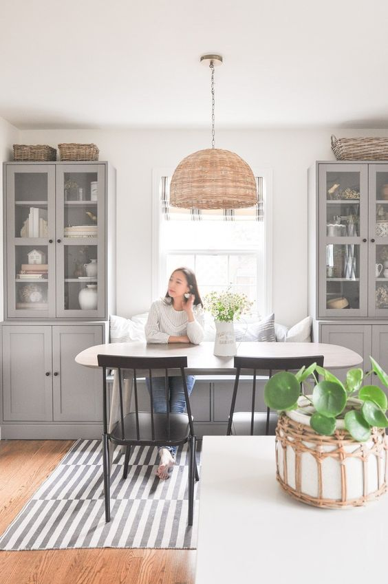 a cozy and welcoming dining room with grey shaker kitchen cabinets, an oval table and black chairs, a pendant lamp