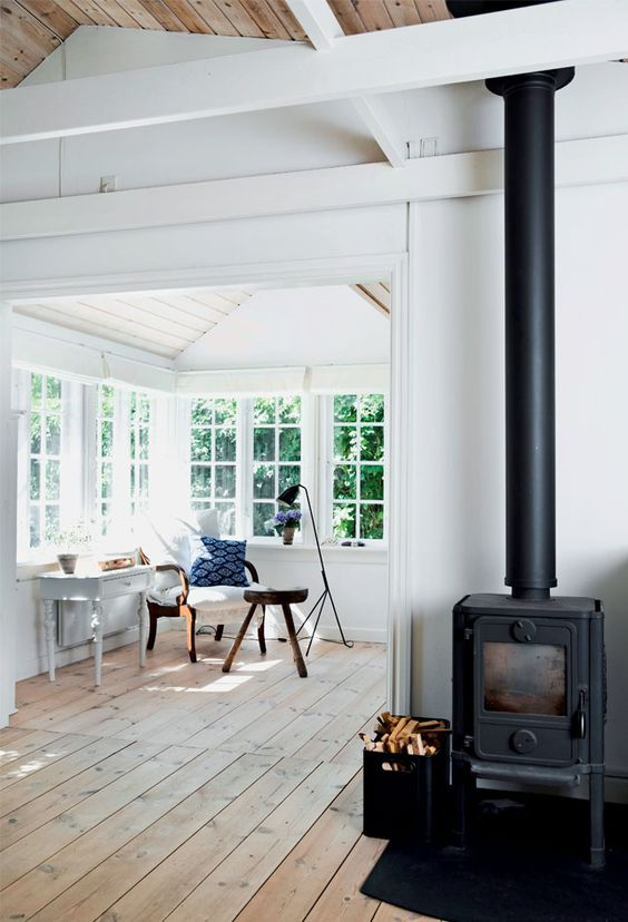 a welcoming Scandinavian space with a corner window flooded with natural light, refined vintage furniture to have a cup of coffee