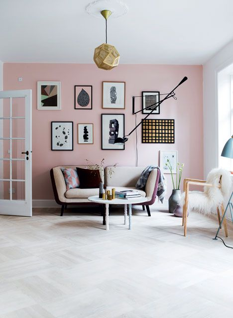 a Scandinavian living room with a light pink accent wall and a gallery wall, a chic sofa, a wooden chair and a coffee table plus a faceted lamp
