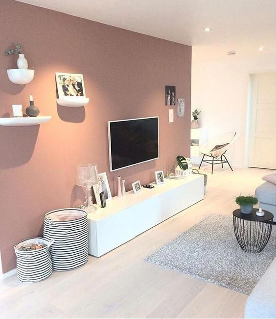a Scandinavian living room with a mauve accent wall, a sleek TV unit, some fabric baskets and shelves for decor on the accent wall