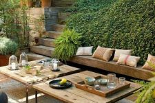 a beautiful and welcoming sunken terrace with greenery, built-in benches and low tables plus poufs is an amazing outdoor space