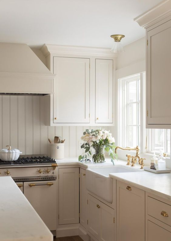 a beautiful creamy modern country kitchen with vintage-inspired cabinetry, a planked backsplash, gold touches and neutral countertops