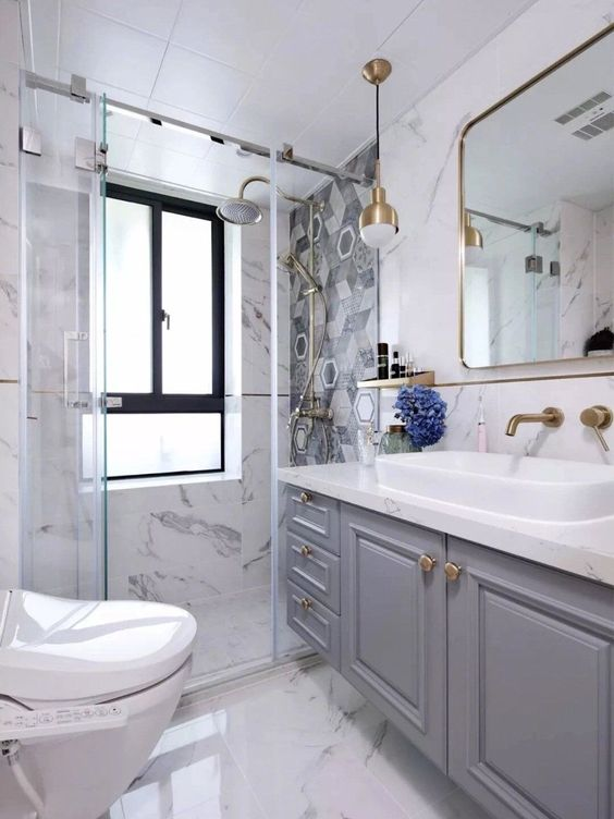 a beautiful fancy bathroom with white marble, a mosaic tile wall in the shower, a grey vanity, gold touches here and there