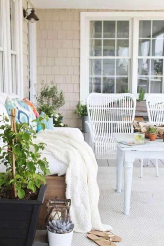 a beautiful farmhouse patio with a wodoen sofa and white rattan chairs, a vintage table, potted plants, colorful bedding and pillows