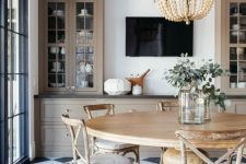a beautiful modern country dining room with a checked floor, a round table, vintage chairs, a wooden bead chandelier and storage cabinets