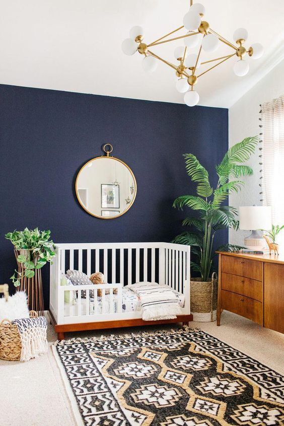 a beautiful modern nursery with a navy accent wall, chic mid-century modern furniture, a printed rug, a basket for storage, potted plants and a chic chandelier