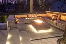 a beautiful sunken pation with built-in lights, a fire pit and lots of pillows invites to spend time here