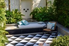 a beautiful sunken terrace with black and white tiles on the floor, built-in benches of concrete, a fountain and lots of greenery