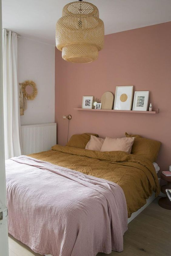 a boho bedroom with a dusty pink accent wall, a bed and a shelf over it, a woven pendant lamp and some pretty pink bedding is chic