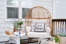a boho farmhouse patio with a striped rug, a wicker egg-shaped chair, some baksets, potted blooms and a rustic side table with blooms