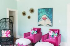 a bold and whimsical living room with a patterned ceiling, hot pink chairs and stools, a bold printed artwork and a bold printed rug