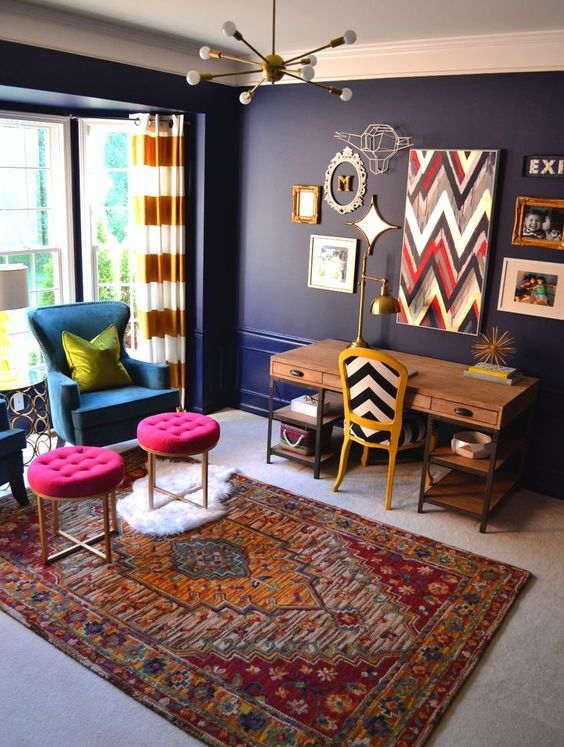 a bold home office with navy walls, a wooden desk, a blue chair and hot pink stools and a bold gallery wall
