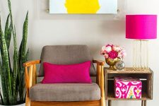 a bold interior with a grey chair, a crate side table, a potted plant, a bright artwork and touches of hot pink in accessories