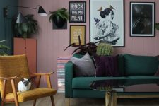 a bold living room with a pink planked accent wall, a dark green sofa and a wall, a mustard chair, some greenery and touches of black for drama