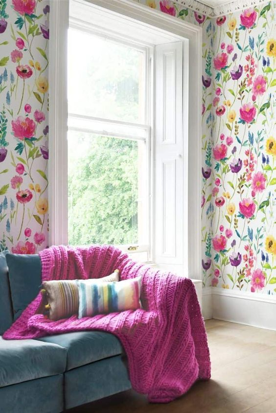 a bold living room with floral wallpaper, a teal sofa and a hot pink blanket that echoes with the floral patterns on the wall