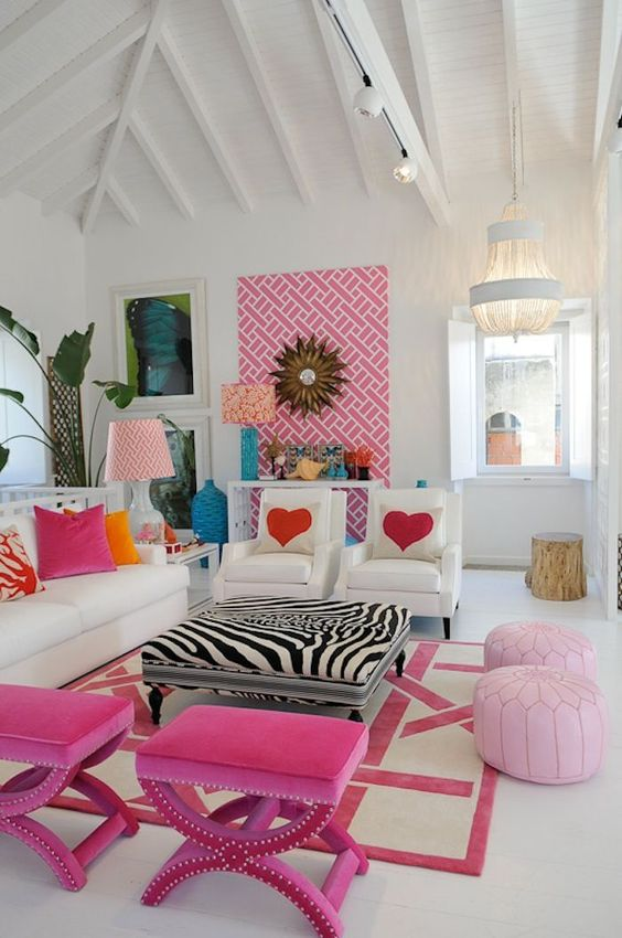 a bright and fun living room with white furniture, hot pink stools and pale pink poufs, a bold artwork and bold printed pillows