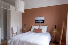 a catchy bedroom with a mauve accent wall, a comfy bed, woven floor lamps and a pendant lamp with a white lampshade