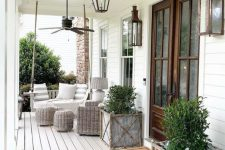 a charming farmhouse porch with a hanging bench with striped pillows, a wicker chair and poufs, plants in wooden boxes and rustic vintage lanterns