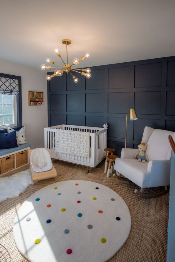 a cheerful nursery with a navy paneled wall, white furniture, a bench with storage, layered rugs and a cool modern chandelier