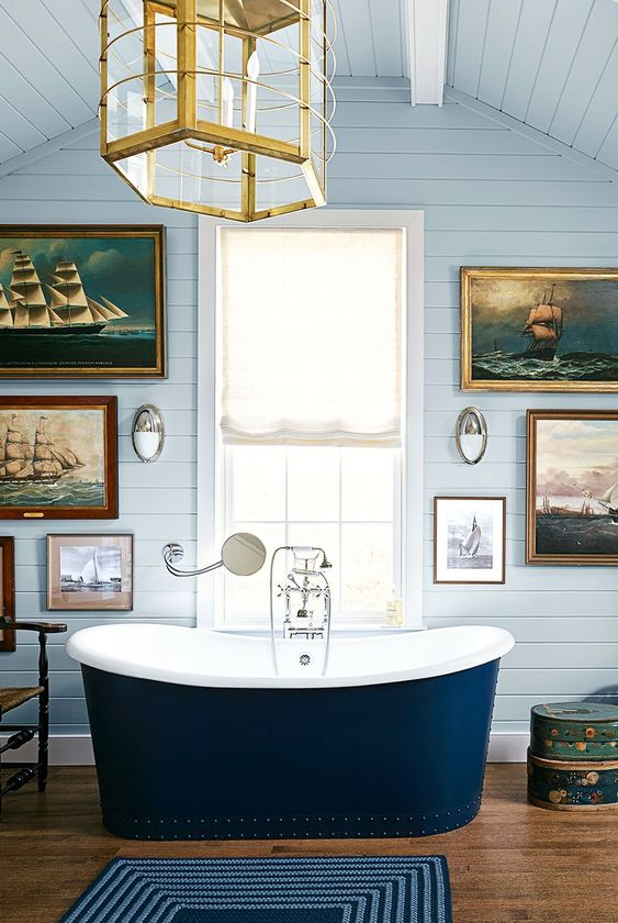 a chic and fancy bathroom with light blue planked walls, a navy tub and a fantastic marine gallery wall plus a glam gold lamp