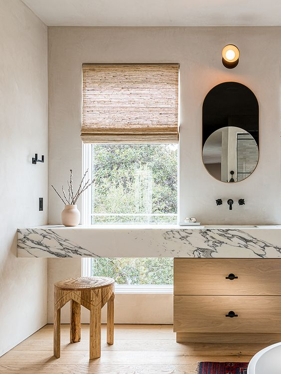 a chic contemporary bathroom with a light-stained and marble vanity, a wooden stool and some decor looks refined and beautiful