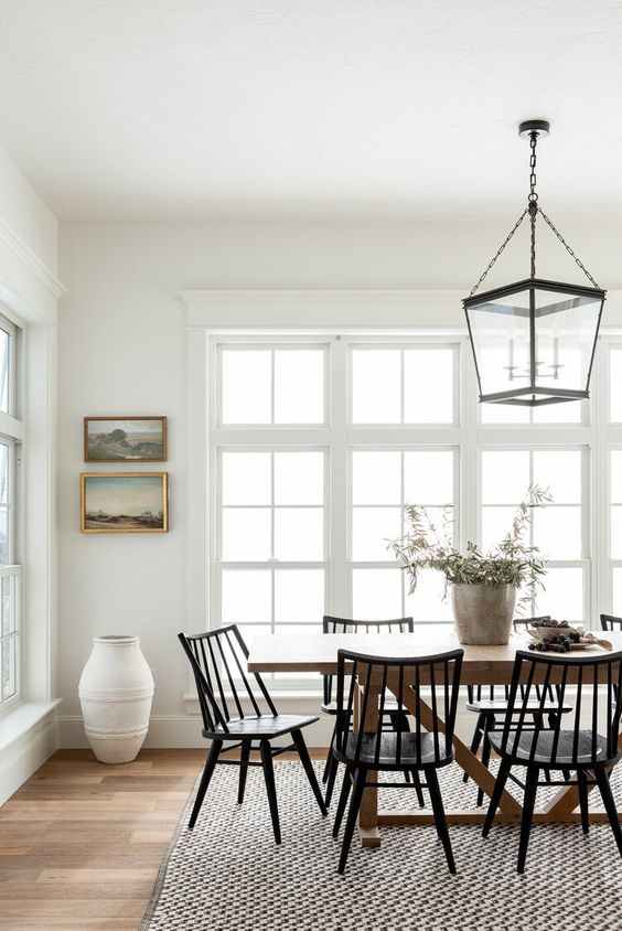 a chic country dining space with a stained dining table, black chairs, a vintage chandelier and a small gallery wall